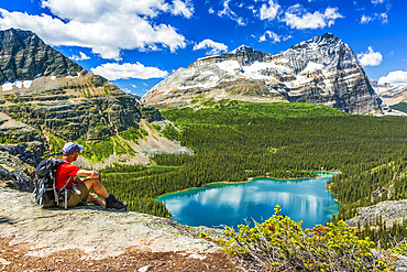Male hiker sitting on rocky ridge overlooking blue alpine lake and mountains in the distance with blue sky and clouds, Yoho National Park; Field, British Columbia, Canada