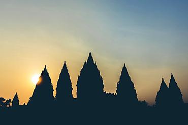 Sunset at Prambanan Temple with silhouetted peaks; Yogyakarta, Indonesia