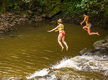Two women wearing bikinis cliff jumping from the top of one of the Twin Falls waterfalls; Haiku, Maui, Hawaii, United States of America