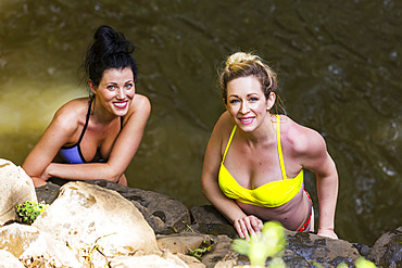 Two women wearing bikinis standing in a pond at the base of one of the Twin Falls waterfalls and looking up at the camera; Haiku, Maui, Hawaii, United States of America