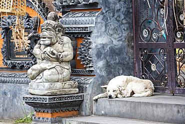 Dog sleeping by a temple; Kamasan, Bali, Indonesia