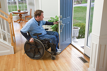 Man in a wheelchair opens the front door of his home and looks out