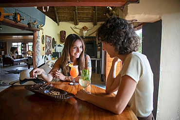 Two women travelers sitting at a table in the bar talking and drinking at the Gabus Game Ranch; Otavi, Otjozondjupa, Namibia