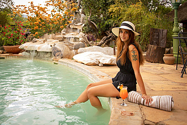 Woman wearing sunhat sitting by a swimming pool dangling feet in the water and smiling at the camera at the Gabus Game Ranch; Otavi, Otjozondjupa, Namibia