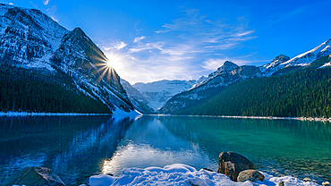 Lake Louise reflecting the Rocky Mountains with a sunburst shining behind a mountain and snow in autumn, Banff National Park; Alberta, Canada