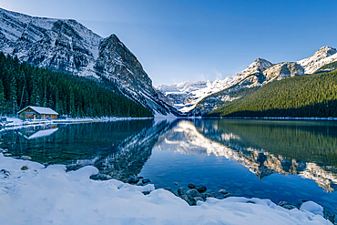 Lake Louise reflecting the Rocky Mountains with snow in autumn, Banff National Park; Alberta, Canada