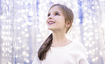 A young girl looks in wonder at white sparkling lights; Studio