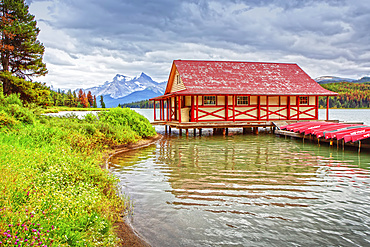 A building and canoes lined up on a dock on Maligne Lake in Jasper National Park in the Rocky Mountains; Alberta, Canada