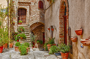 Exterior of an old, stone building with a staircase and three entrances to separate apartments with terracotta flower pots on the terrace as well as suspended on the stone walls; Volterra, Province of Pisa, Tuscany, Italy