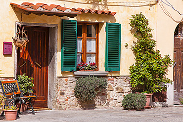 Traditional stucco home with wooden front door and window with green shutters on a sunny day in the town of Cortona; Arezzo, Tuscany, Italy