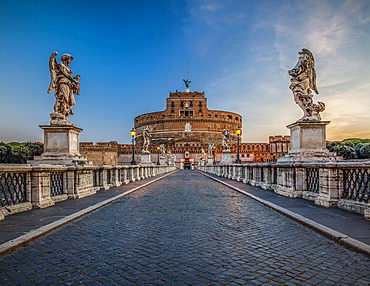 Ponte Sant'Angelo spanning the Tiber River and lined with statues of angels leading to the Castel Sant'Angelo (Mausoleum of Hadrian) at dusk; Rome, Lazio, Italy