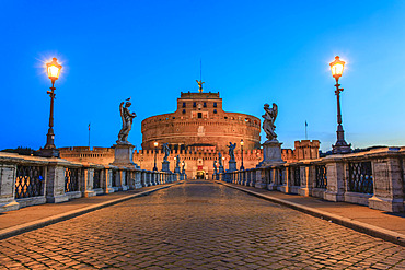 Ponte Sant'Angelo spanning the Tiber River and lined with statues of angels illuminated by lampposts at dusk and leading to the Castel Sant'Angelo (Mausoleum of Hadrian); Rome, Lazio, Italy