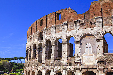 Close-up view of the iconic Colosseum against a blue sky, showing a marble plaque  above the East Entrance dedicated to Christian martyrs; Rome, Lazio, Italy