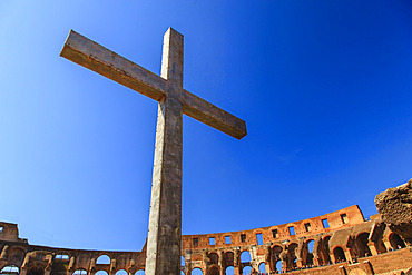 Close-up of a Christian cross inside the Roman Colosseum against a blue sky, erected by the Pope in 2000 to commemorate Christian Martyrs; Rome, Lazio, Italy