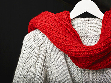 A grey knit sweater draped with a red knit scarf displayed on a hanger on a black background; Studio