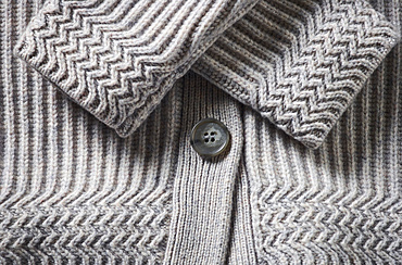 Extreme close-up of the cuffs and button on a grey knit sweater; Studio