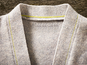 Collar and neckline of a grey cardigan sweater with yellow stitching; Studio