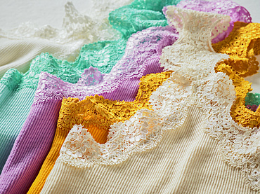Colourful pieces of clothing with lace trim lay in a pile; Studio