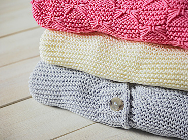 Three knit sweaters folded in a pile; Studio