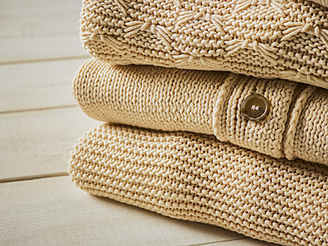 Three beige knit sweaters folded in a pile; Studio