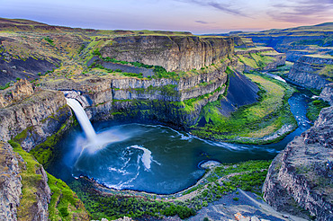 Overview of the Palouse Falls surrounded by basalt rock, a remnant of ancient glacial floods and lying on the Palouse River within the Palouse Falls State Park at sunset; Washington, United States of America