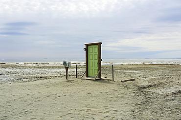 Bombay Beach door sculpture art on beach with Salon Sea in background; Bombay Beach, California, United States of America