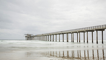 The long expanse of the iconic Scripps Pier in the Pacific Ocean near San Diego on a grey day; La Jolla, San Diego County, California, United States of America