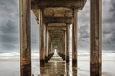 Stormy sky and the repeating view of the cement columns under the iconic Scripps Pier in the Pacific Ocean near San Diego; La Jolla, San Diego County, California, United States of America