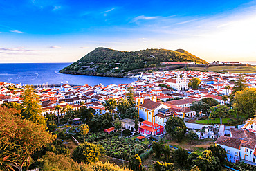 Scenic view overlooking Monte Brasil and the capital city of Angra do Heroismo,  with the sunset reflecting warm light on the whitewashed buildings and the brilliant blue Atlantic Ocean; Terceira, Azores