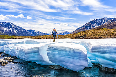 Woman hiking along the Dempster Highway enjoying the scenery, and standing on a piece of late season ice along the Klondike River in Tombstone Territorial Park; Yukon, Canada