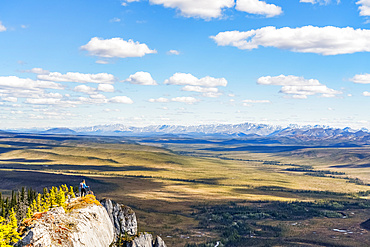 Woman hiking along the Dempster Highway enjoying the scenery on top of Sapper Hill; Yukon, Canada