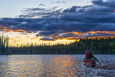 View taken from behind of person canoeing at sunset on a lake near Whitehorse; Yukon, Canada