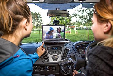 Girls catching up on some videos inside a camper van; Prague, Czech Republic
