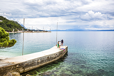 Tourists walk on a pier towards the turquoise water along the coast of Podgora, Croatia. This group has stopped for an early morning swim and shower after camping in their van; Podgora, Split-Dalmatia County, Croatia