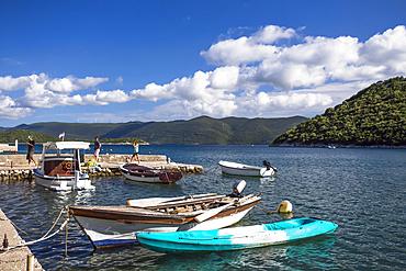 Young adult tourists at the waterfront of Duboka with rowboats and motorboats mooring in the water; Duboka, Dubrovacko-neretvanska zupanija, Croatia