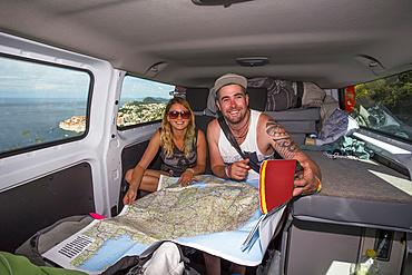 Travelers inside a camper van looking over a map for directions while exploring the cliffs surrounding Dubrovnik providing stunning views of the coastal city; Dubrovnik, Dubrovnik-Neretva County (Dubrovačko-neretvanska županija), Croatia