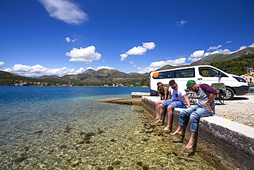 A group of friends sitting outside their camper van as they stop in Slano for an afternoon at the beach; Slano, Dubrovacko-neretvanska zupanija, Croatia