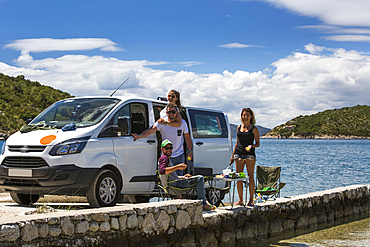 A group of friends standing and eating in the sun outside their camper van as they make a stop in Slano for an afternoon at the beach; Slano, Dubrovacko-neretvanska zupanija, Croatia