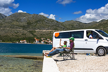 Friends sitting in the sun resting outside of a camper van as group of travelers stop in Slano for an afternoon at the beach; Slano, Dubrovnik-Neretva County (Dubrovačko-neretvanska županija), Croatia