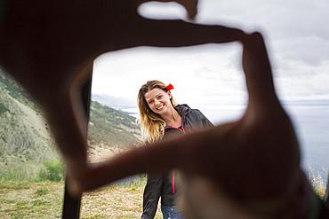 Framing a beautiful girl with fingertips with the Croatian coastline in the background; Pisak, Splitsko-dalmatinska zupanija, Croatia
