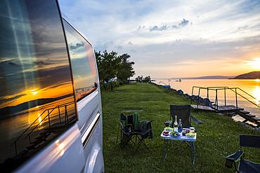A group of travellers set up camp alongside of Lake Balaton at sunset; Zamardi, Somogy County, Hungary