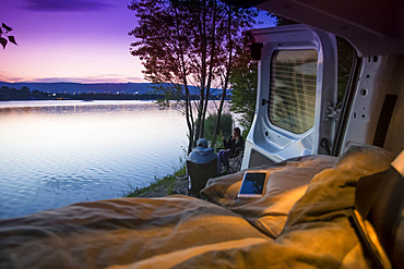 Travelers pull up alongside a lake in Bratislava to free camp for the night. A view from the bed in the back of the camper van; Bratislava, Bratislava Region, Slovakia