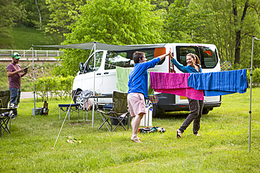 Campers playing badminton next to their camper van at a campsite just outside of the city center of a beautiful medieval city in South Bohemian Region; Cesky Krumlov, Bohemia, Czech Republic