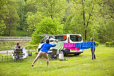 A group plays badminton at their campsite just outside of the town centre of the little medieval city of Cesky Krumlov in the South Bohemian region of Czech Republic; Cesky Krumlov, Bomenia, Czech Republic
