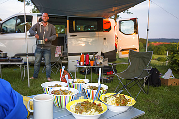 A stop for the night at a Czech Republic campsite between Prague and Cesky Krumlov. The 50 person town is called Kostelec and it is on the outsirts of Hluboka nad Vltavou. A camper sets up dinner at their campsite; Kostelec, Vltavou, Czech Republic