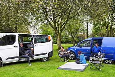 Friends relaxing while setting up camp outside two modified caravan campers; Bourton-on-the-Water, England, United Kingdom