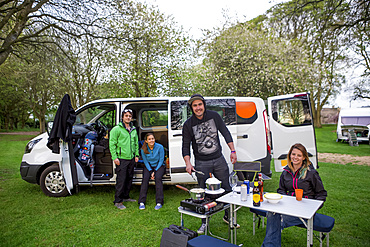 Setting up camp outside of a modified caravan camper; Bourton-on-the-Water,  Gloucestershire, England