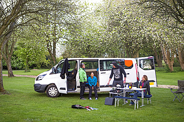 Friends setting up camp outside of a modified caravan camper; Bourton-on-the-Water, England, United Kingdom