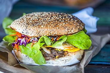 Close-up of a giant hamburger garnished with condiments and vegetables, Abel Tasman National Park; Tasman, New Zealand