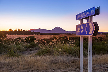 A beautiful sunset in the Tongariro National Park. The volcanic Mount Doom (Mount Ngauruhoe) can be seen in the background, with a roadside sign in the foreground; Manawatu-Wanganui, New Zealand